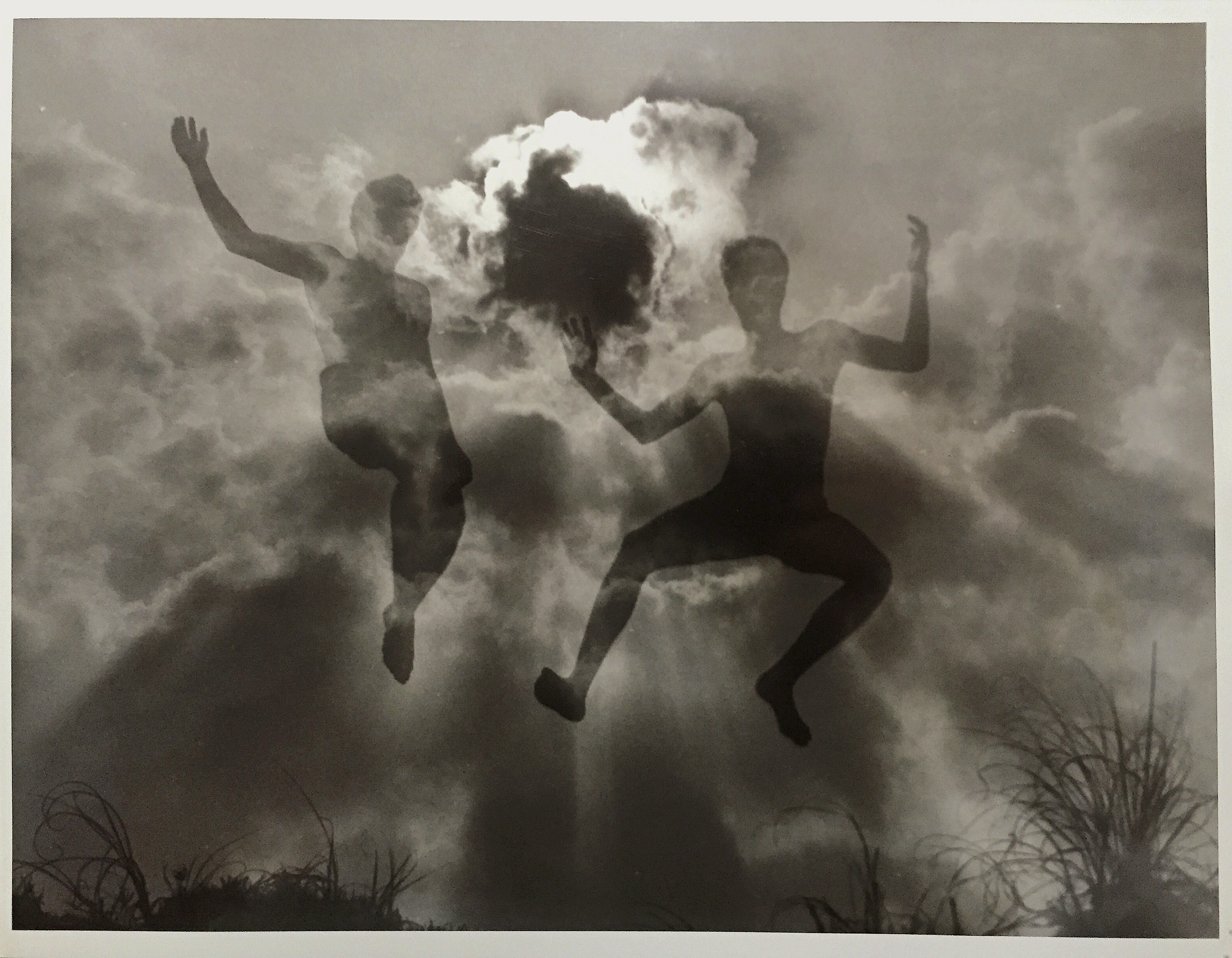 A double exposure of friends in high school jumping off of a sand dune- and clouds